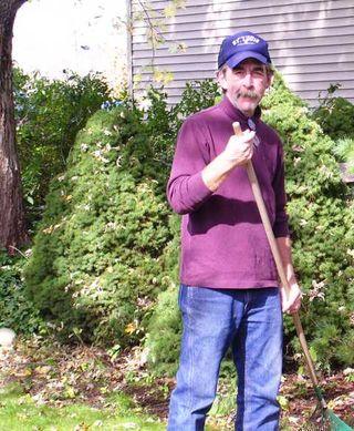Tom raking in backyard
